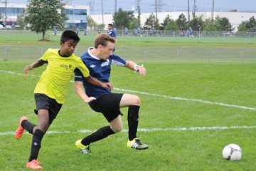 Team ITG (yellow) and Team Mackenzie Investments (blue) face off at the Bay Street Kicks Kids' Cancer Soccer Tournament on  Sept. 19, 2015