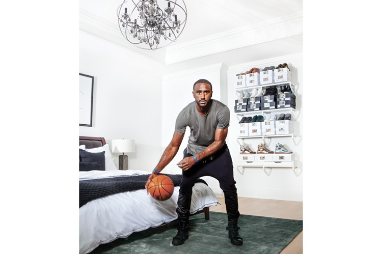 "Patterson shows off his ball handling in his pristine bedroom. A selection of his ""infinite amount of shoes"" is stacked decoratively for effect"