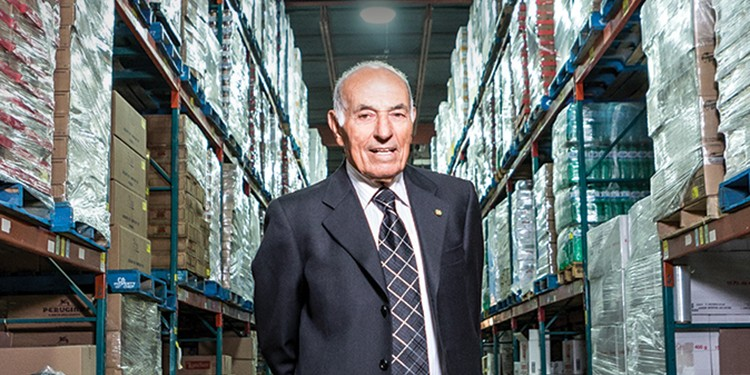 Aurora Importing and Distributing founder Nunzio Tumino stands proudly at the wholesale business's 50,000-square-foot warehouse in Mississauga. The 87-year-old is hailed as  a pioneer in the food-importing industry in Canada