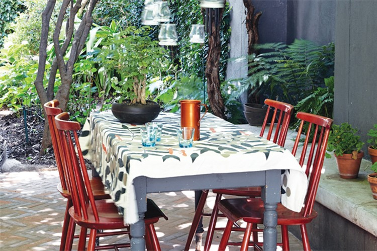 In the dappled light of the grapevine in the back courtyard, behind the dining room and kitchen, the Ercol-style chairs echo the inspiration for Gregor Jenkin's Quaker dining chairs inside. From the courtyard, a path leads through the lush greenery of the garden around the side of the house