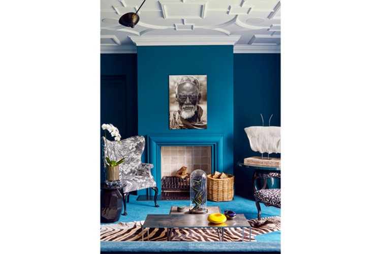 The teal blue wall hue was matched to the custom-coloured Rowley & Hughes carpet in the living room. The ceiling lights are original Serge Mouille