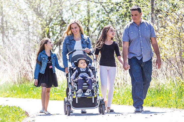 "The Gennuso family gets some fresh air at a nearby park. Parents Laura and Daniel juggle a busy schedule of homework and dance classes alongside Luca's full program of intense therapy sessions. ""It's our new normal,"" says the dad"