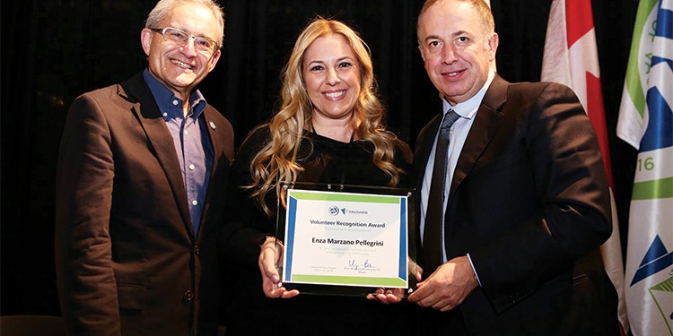 Enza Marzano-Pellegrini, principal of the Montessori School of Kleinburg, is presented with an award for volunteering with The Olive Branch for Children