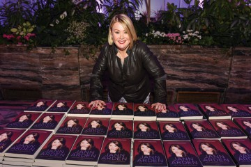Jann Arden poses with copies of her popular novel, Falling Backwards: A Memoir