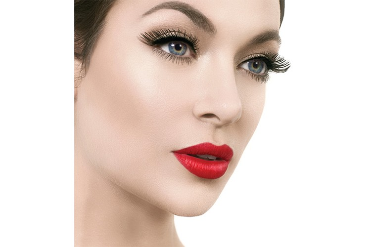 A glamorous combination of red lips and bold false lashes by Rita Stirpe