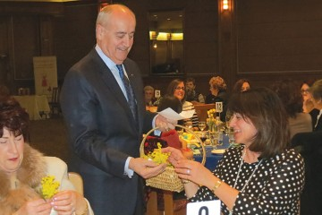 Associate Minister of National Defence Julian Fantino presents hundreds of local women with mimosa flowers on International Women's Day