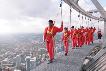 A group of journalists, and a nervous Ford representative, survey Toronto from 356 metres up during the EdgeWalk