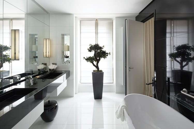 A smooth black counter and Les Marbreries de la Seine wall detail juxtapose pristine flooring and an Aquamass-Stone One bathtub