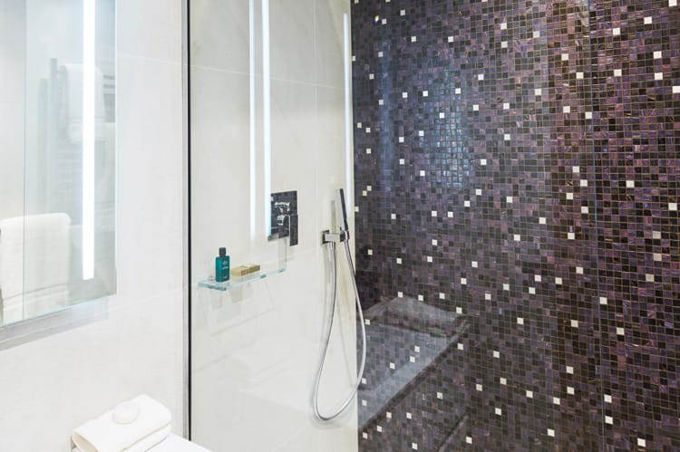 A celestial accent wall by Bisazza gives beautiful contrast to this clean, modern bathroom, which includes a sink and mirror from Cosmic and shower and taps from Gessi.